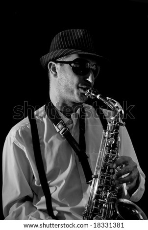 Saxophonist Series: Musician playing in black background - stock photo
