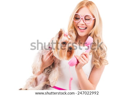 Say hello! Beautiful young blond hair woman carrying Yorkshire terrier in hands and holding telephone near it while standing isolated on white background