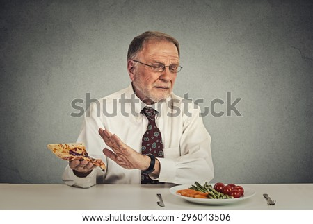 Say no to fast food. Senior man eating fresh vegetable salad avoiding fatty pizza