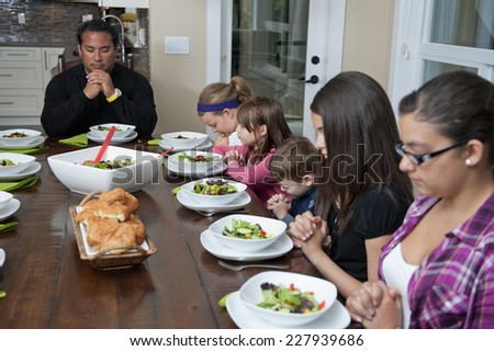 saying grace at meal / a family get together / children fold their hands - stock photo
