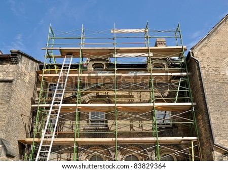 Scaffold erected for reconstruction of college building - stock photo