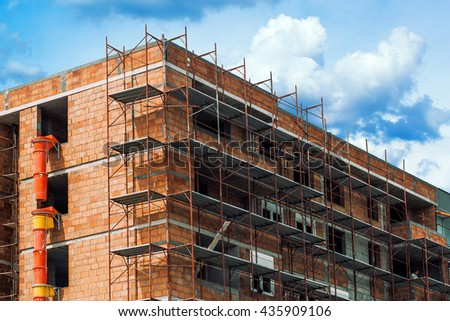 Scaffolding around the unrendered and unplastered building at construction site of new residential apartments district. - stock photo
