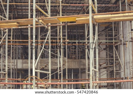 Scaffolding background, elements construction with platforms for work at construction site. Abstract under construction. Vintage style.