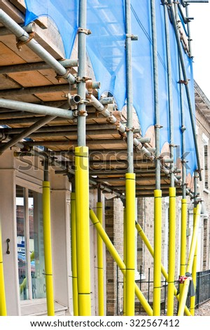 Scaffolding bars on the outside of a house, with padding for safety of pedestrians - stock photo