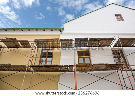 Scaffolding covering a facade of an old building  under renovation  - stock photo