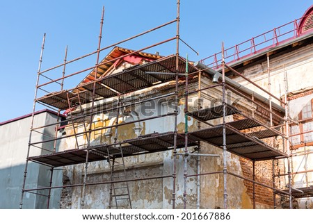 Scaffolding covering a facade of an old building  under restoration - stock photo
