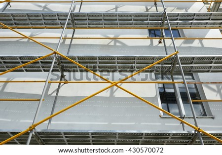 scaffolding near a house under construction for external plaster works, high apartment building in city, white wall and window, yellow pipe - stock photo