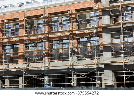 Scaffolding used in front of a city apartment which is under construction. - stock photo