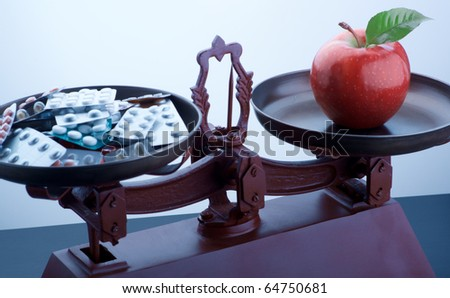 Scale with apple and medicine - stock photo