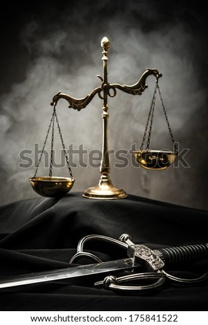 Scales and sword of Justice on a judge's mantle - stock photo