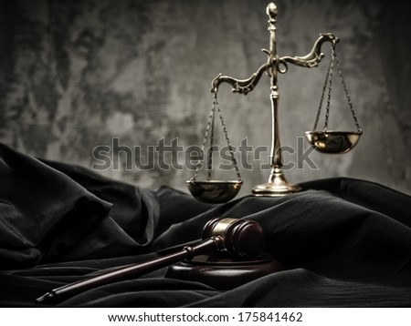 Scales and wooden hammer on judge's mantle  - stock photo