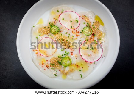 Scallop Carpaccio with espellete pepper, lemon, extra virgin olive oil, serrano chiles and pickled mustards seeds - stock photo