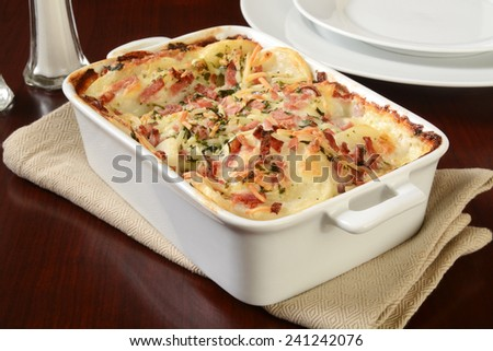 Scalloped potatoes in cheese sauce with ham in a casserole dish - stock photo