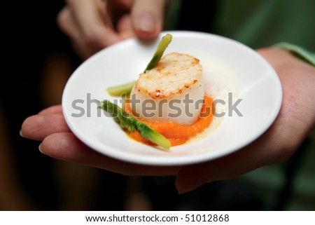 Scallops with asparagus and molecular froth in woman's hands - stock photo