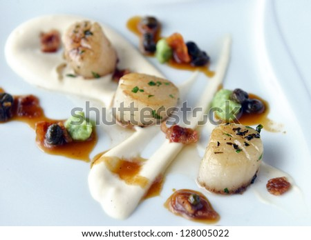 scallops with bacon and sauce on a plate - stock photo