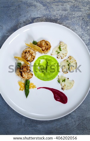 Scallops with beetroot, pea and cauliflower puree, asparagus and parmesan crisp - stock photo