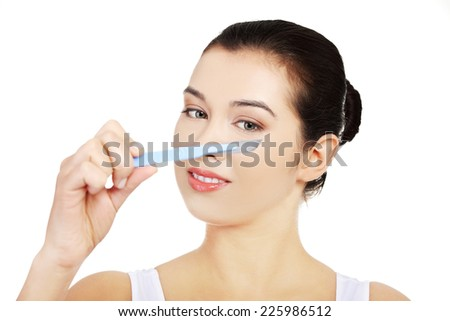Scalpel near beautiful woman's face - stock photo