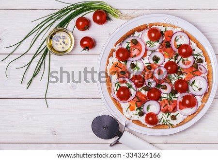 Scandinavian salmon pizza with cream cheese, capers, tomato and onion. Top view. - stock photo