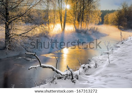 Scandinavian small river in winter, with sunbeams filtering through bare birch trees - stock photo