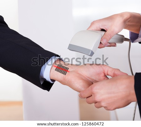 Scanning barcode on the hand using scanner - stock photo