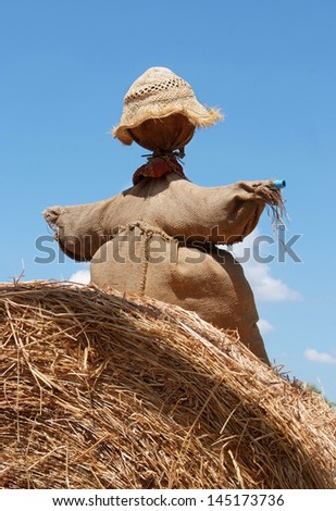 Scarecrow sitting on a pile of straw with blue sky in summer.  - stock photo