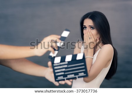 Scared Actress Shooting Movie Scene  - Young professional cinema star acting sad in a drama film  - stock photo