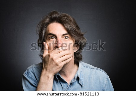 scared adult man with hand covering mouth and dramatic lighting - stock photo