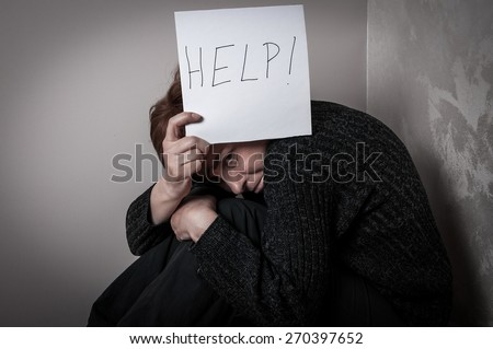 Scared and abused woman holding the paper with handwritten help sign. Low key - stock photo