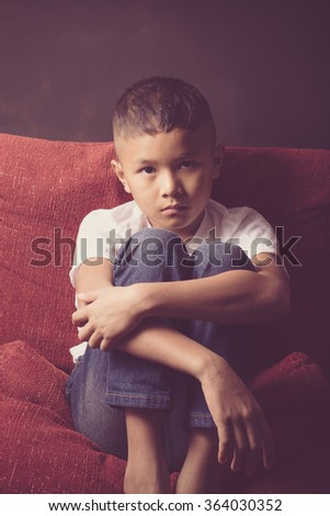scared and alone, young Asian child who is at high risk of being bullied, trafficked and abused