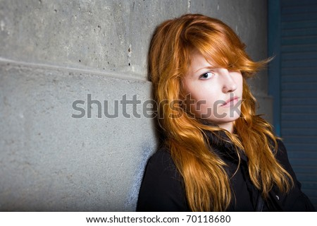 Scared and lonely, moody portrait of a beautiful fashionable young redhead girl. - stock photo