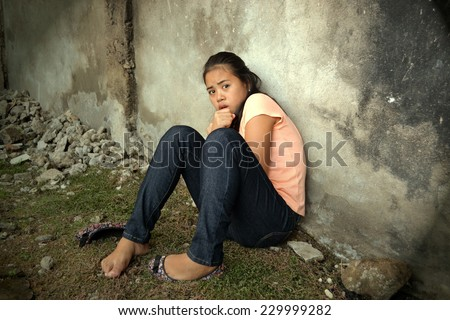 Scared Asian young lady leaning on a wall in a poor area looking at something with fear - stock photo