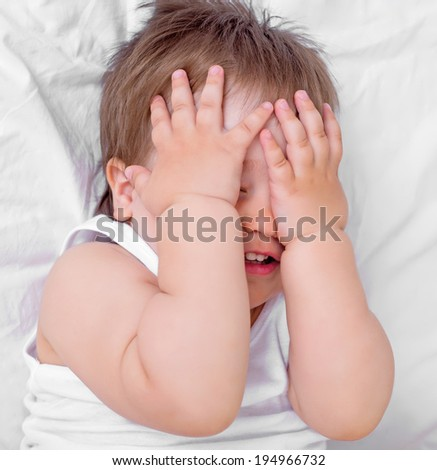 scared baby closing his face with hands, in bed at home, top view - stock photo