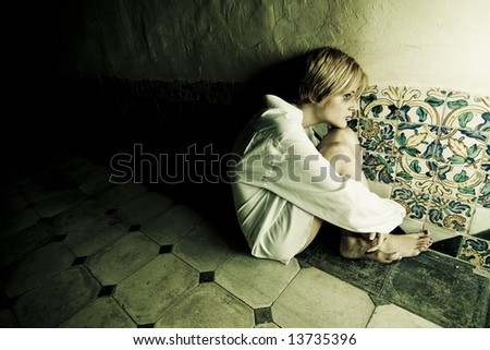 Scared blond woman on wall - stock photo