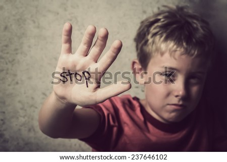 Scared boy with Stop written on his hand - stock photo