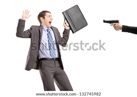 Scared businessman from a hand holding a gun - stock photo
