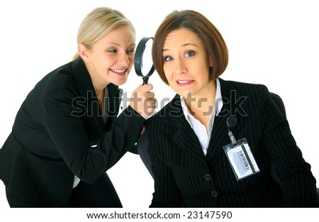 scared Caucasian businesswoman under close watch by other business investigator - stock photo
