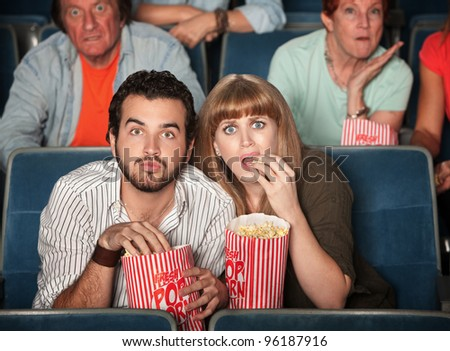 Scared Caucasian couple eating popcorn in theater - stock photo