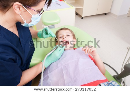 Scared child on drilling procedure in dentist chair. Female or woman dentist doctor working with kid patient - stock photo