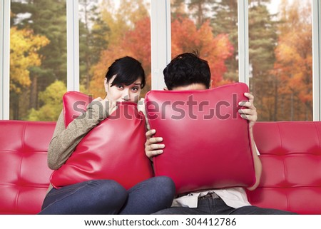Scared couple covering their face while watching horror movie at home - stock photo