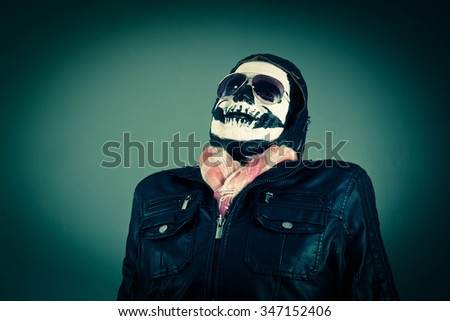 Scared Disapproving aviator with face painted as human skull - stock photo