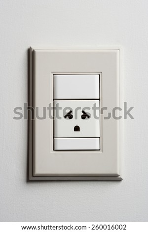 Scared Electric Wall Power Outlet on a White Wall. Outlet Expression Looks like It's Scared or Frightened - stock photo