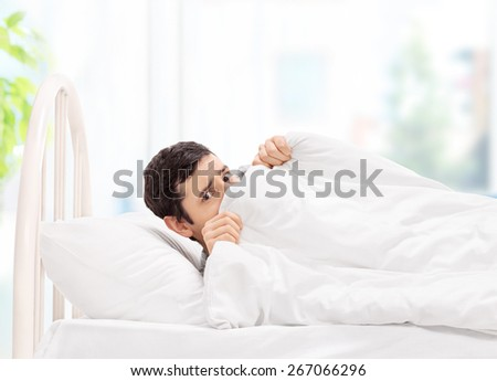 Scared guy lying in bed and hiding under a blanket at home - stock photo