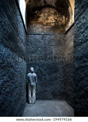 Scared, insane woman hiding in a corner of an ancient building. - stock photo
