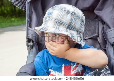 scared little boy covers mouth with her hand - stock photo