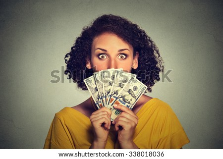 Scared looking woman hiding picking through dollar banknotes  - stock photo