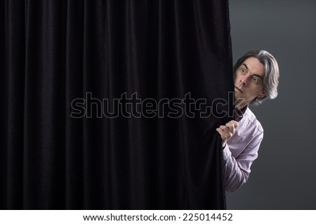 Scared man hiding behind a curtain. - stock photo