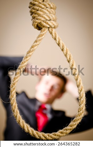 Scared man in suit with hanging noose - stock photo