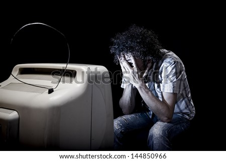 scared man is watching tv  through his fingers all alone - stock photo