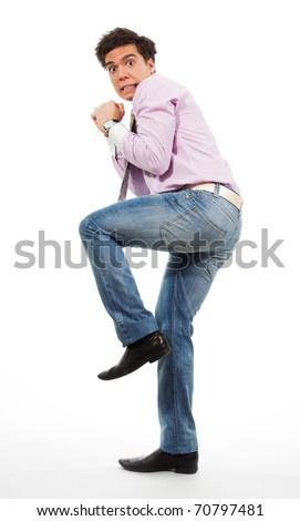 Scared man running away with grimace in his face wearing jeans, shirt and tie