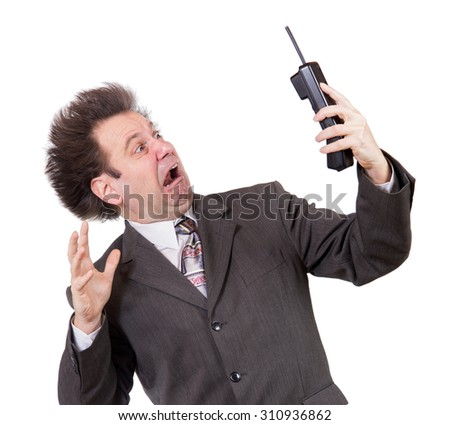 Scared man with phone. The frightened man in a suit has bristling hair and looks at the telephone in his hand. Shocked businessman calling on the phone isolated on white background.